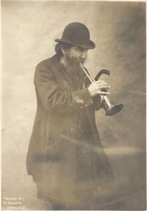 Street musician plays trumpet, Lancaster, UK, c. 1908 (image)